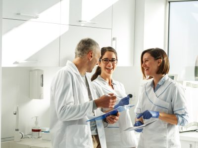 Medical dentist team in dental office discuss about practice and examining list of patients.